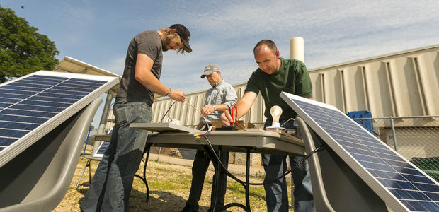 Teachers Andrew Richard, left, of Black River Falls High School and Andy Udell, right, of Janesville Craig High School set up a solar panel system with instructor Joel Shoemaker earlier this month at the Wisconsin Solar Educator Academy at Madison Area Technical College.