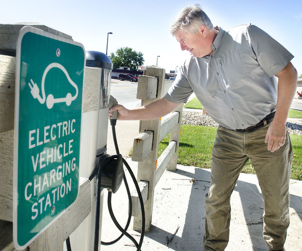 South Sioux City senior code official Kent Zimmerman demonstrates the electric-car charging station in front of City Hall. The northeast Nebraska city has four electric cars, part of its push to use more renewable energy. Photo by Justin Wan, Sioux City Journal