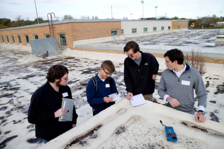 Creighton University students, from left, Jon Lundin, Anton Yanchilin, Parker Revier and Sam Rosol are conducting energy audits, including running tests for solar panels, at local schools as part of their capstone project. Photo: Sarah Hoffman / The World-Herald